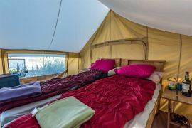 comfy beds in waterfront tent