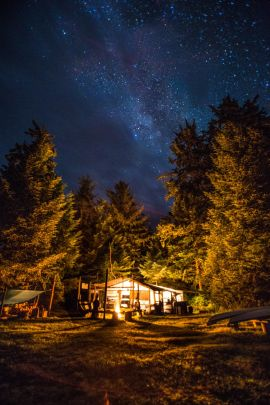dining and activity shelter lit up under starry sky