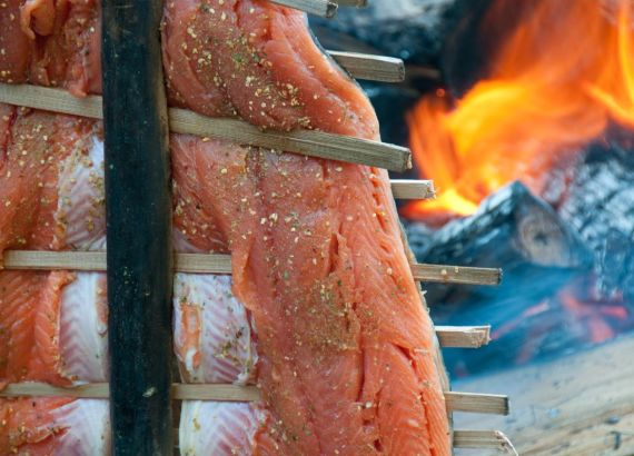 salmon cooking beside fire